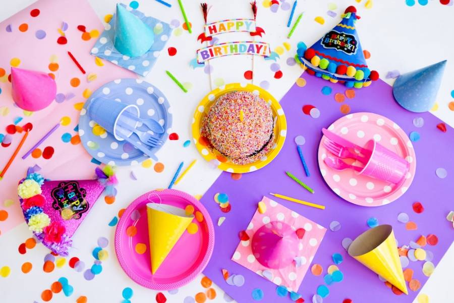 Kids birthday party table with cake, hats and confetti