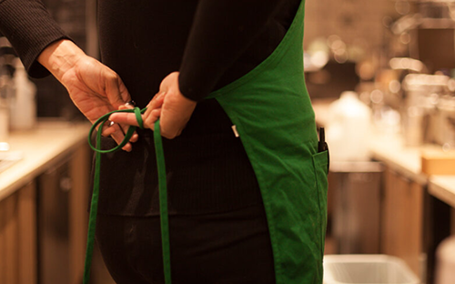 Person tying green Starbucks apron