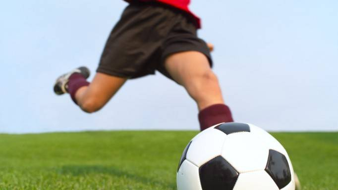 Child kicking football